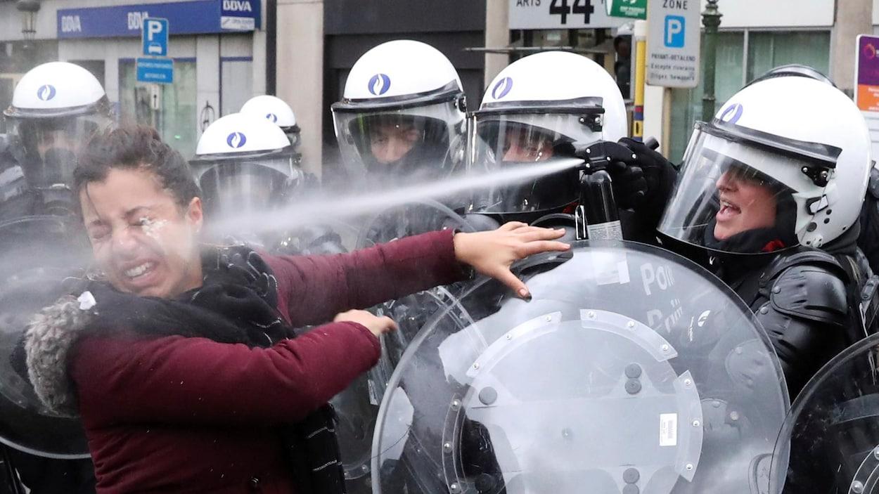 Une femme reçoit du gaz lacrymogène en pleine figure, lancé par une policière avec un bouclier.