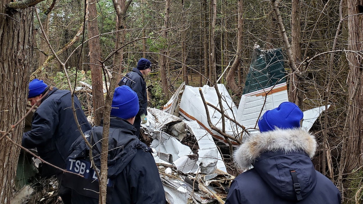 Des enquêteurs sont sur le lieu d'un écrasement d'avion dans une zone boisée avec les débris d'un avion.