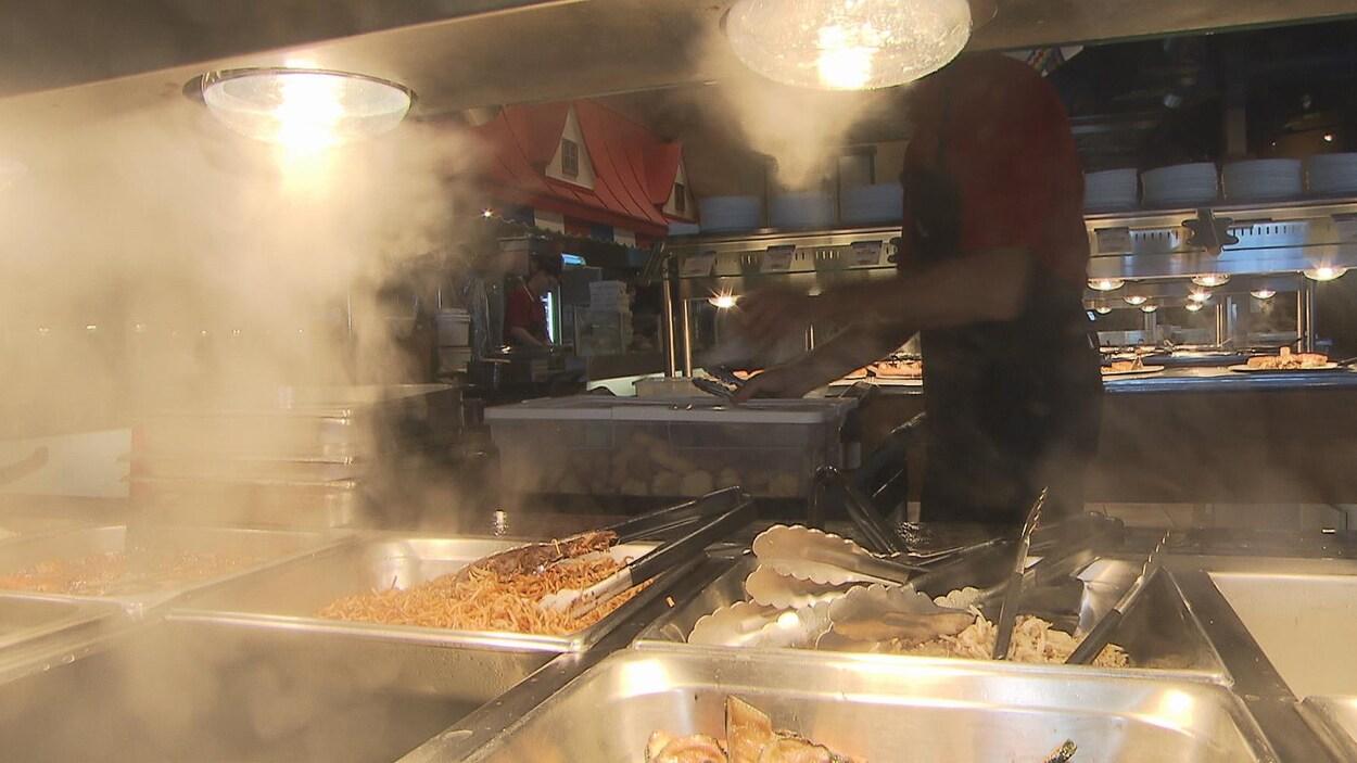 Un employé du Buffet des Continents met la nourriture non consommée dans des contenants à emporter pour les transporter vers un organisme de bienfaisance.