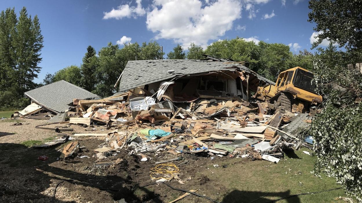 La maison semble avoir été complètement détruite par une tornade, sauf que le bulldozer qui l'a mise à terre se trouve juste à côté.