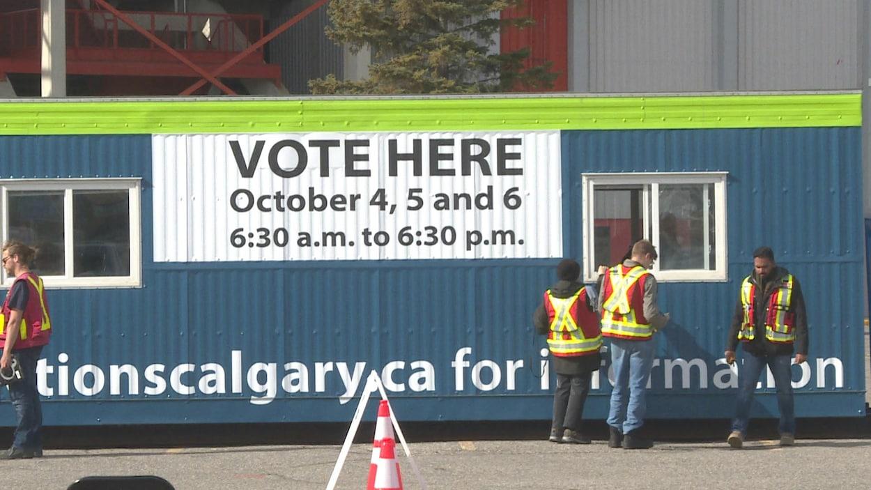 Des travailleurs devant un conteneur transformé en bureau de scrutin