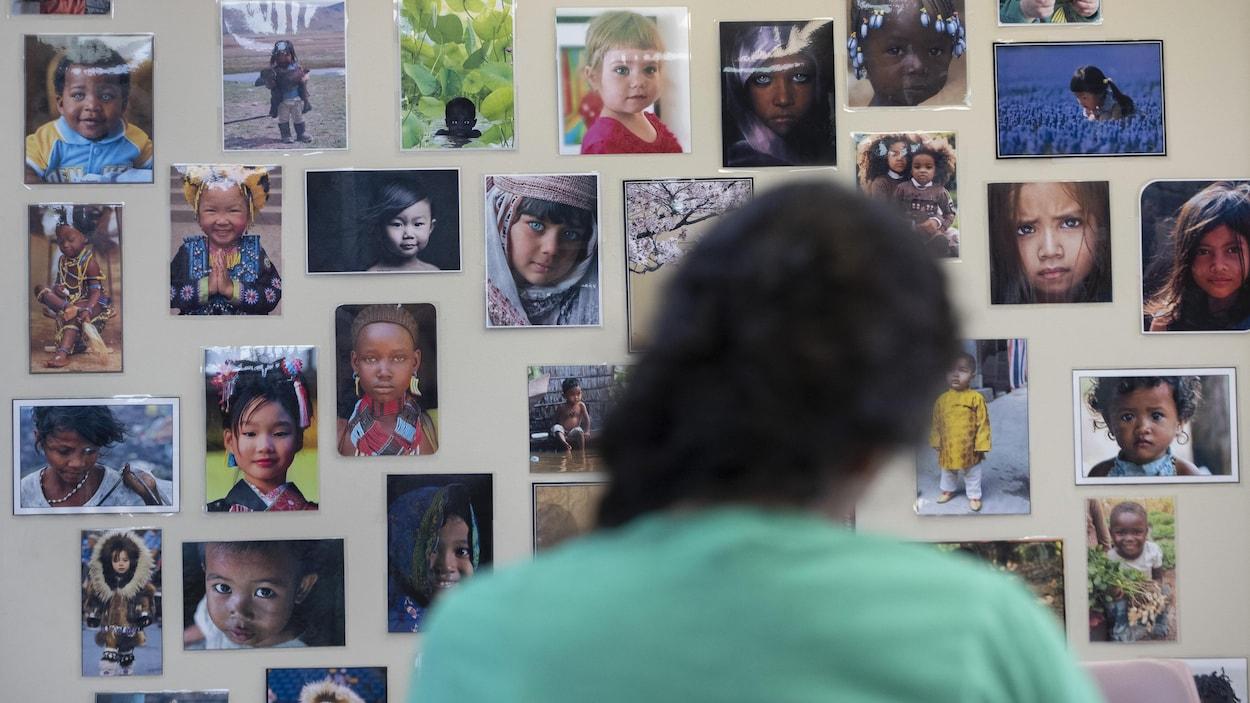 Une jeune femme de dos, et devant elle, un mur décoré de photos d'enfants des quatre coins du monde.