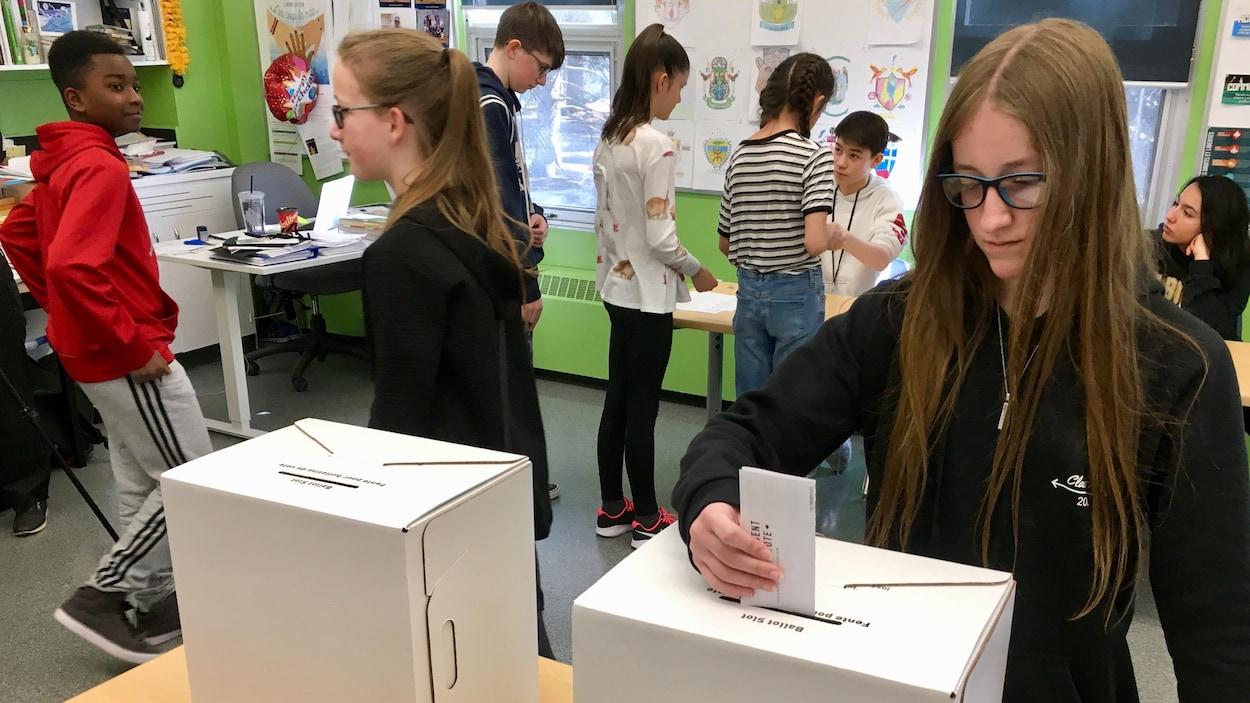 Une jeune fille aux cheveux longs et à lunettes dépose un papier dans la fente d'une boîte en carton posée sur une table. Une autre boite en carton est posée à côté. Derrière, des jeunes sont en ligne et semblent attendre leur tour.