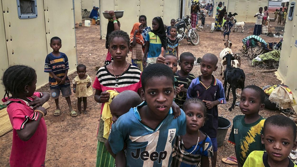 Des enfants rassemblés devant l'objectif de la caméra dans un camp de réfugiés.