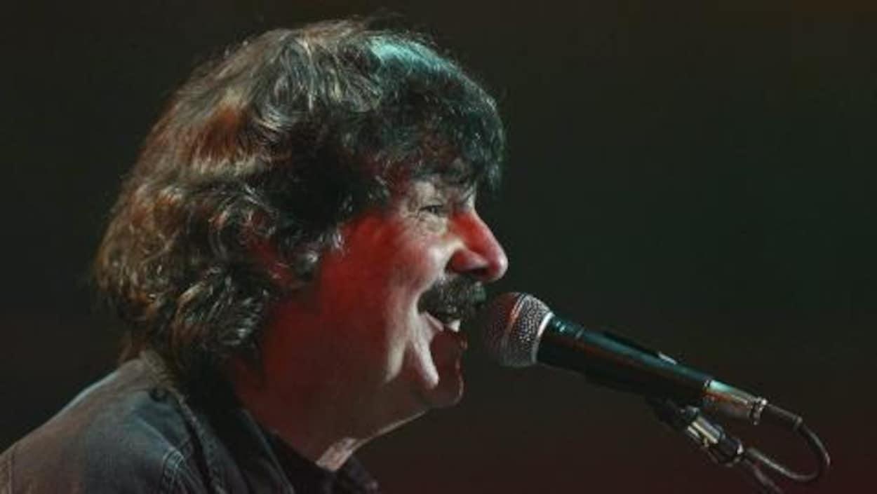 Burton Cummings, devant un micro, chante pendant un concert.