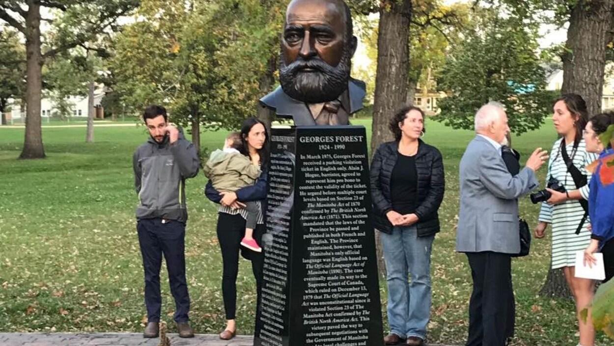 Des gens réunis autour d'un buste en bronze.