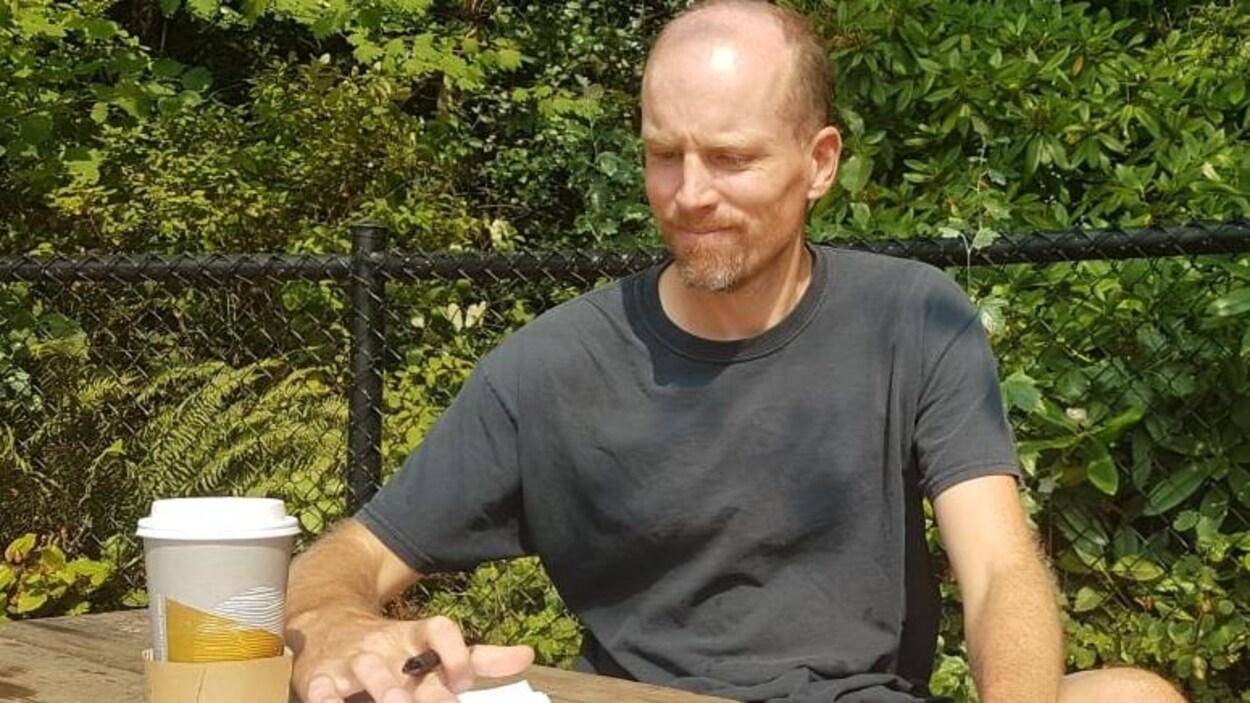 Un homme le crâne dégarni assis à une table de pique-nique avec un stylo à la main et une tasse de café posé sur son calepin