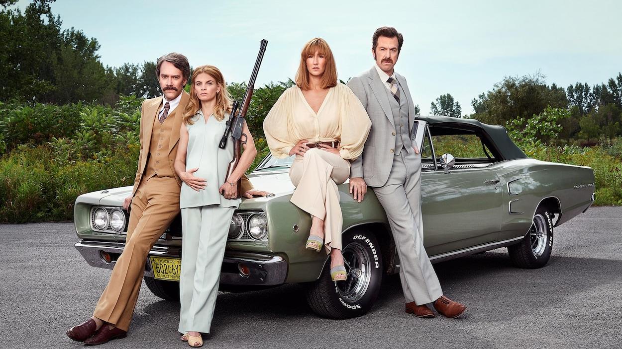 Les actrices et acteurs posent habillés et coiffés à la mode des années 1970 devant une voiture de l'époque.