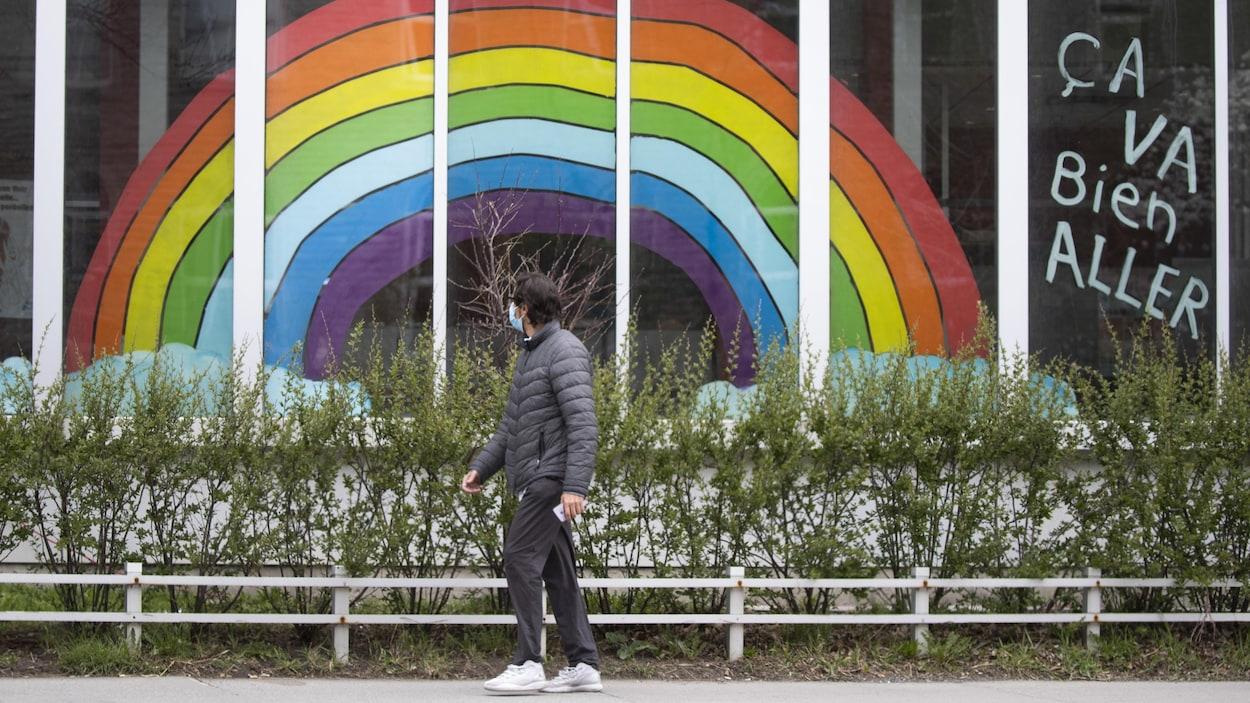 Un homme passe devant une fenêtre où est affiché un énorme dessin d'arc-en-ciel.