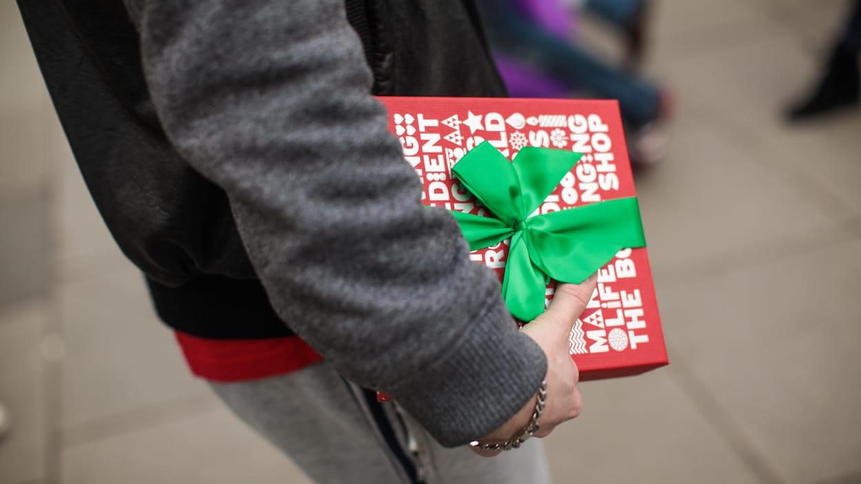 Un consommateur tient son cadeau de Noël.