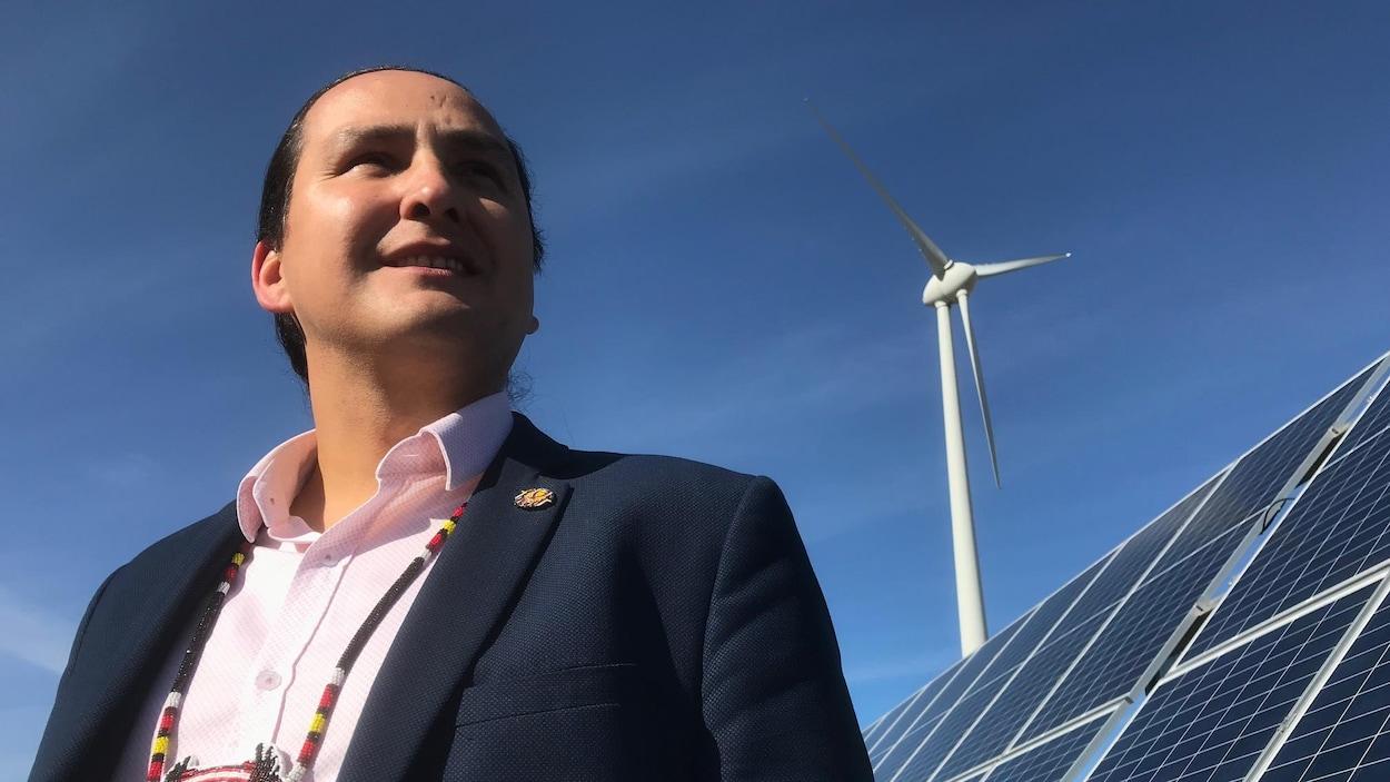 Un homme avec un collier traditionnel autochtone devant un panneau solaire et une éolienne