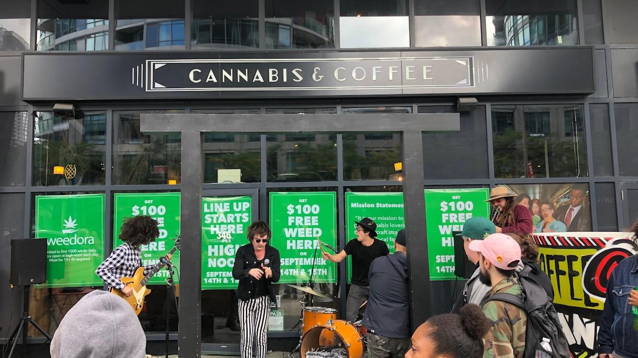 Un groupe de musiciens joue devant un café Cannabis & coffee.