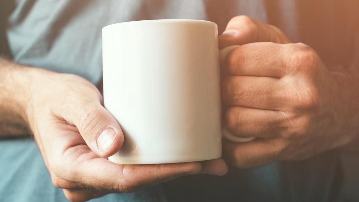 Un homme tient une tasse de café.