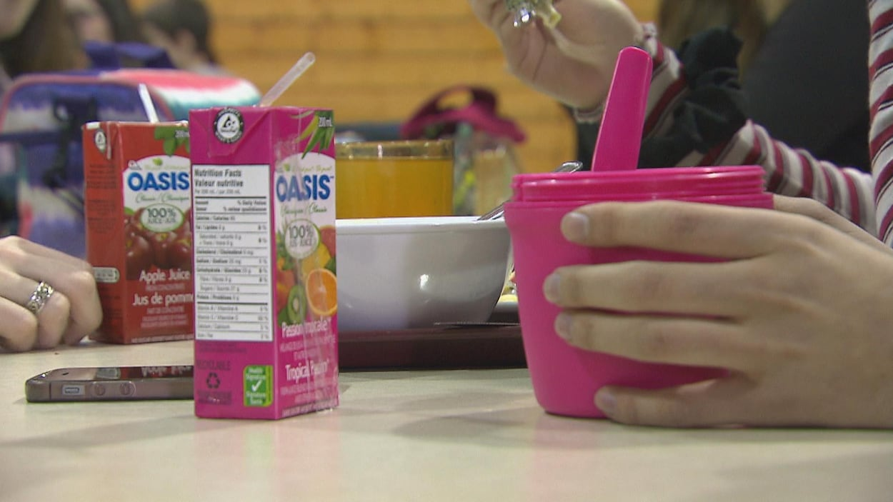 Des boites de jus et des mains en gros plans durant un repas.