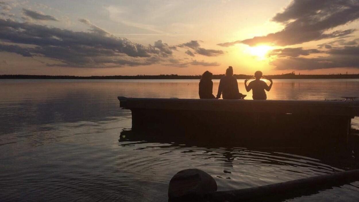 Des membres de la communauté de La Loche regardent le coucher de soleil devant le lac.