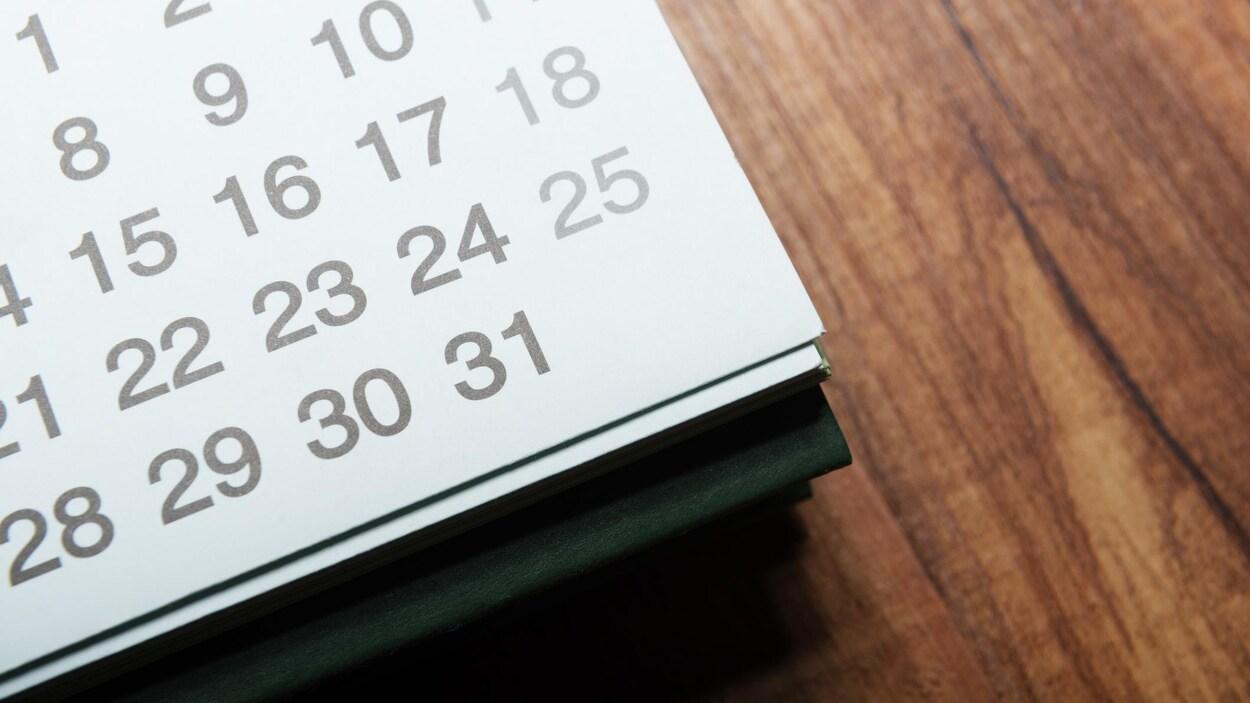 Un calendrier posé sur une table en bois.