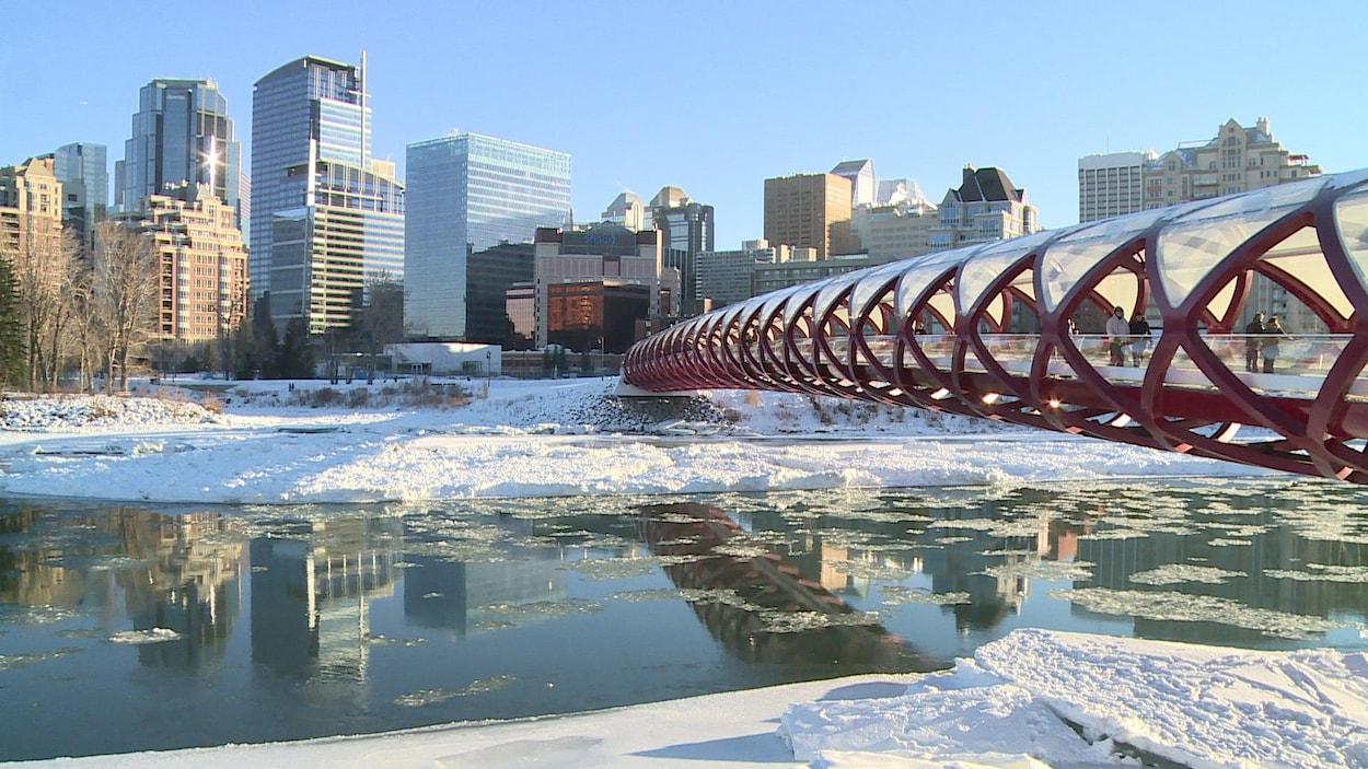 Photo de la rivière Bow en hiver. Des morceaux de glace flottent sur la rivière. À droite, on voit le pont Peace et le centre-ville en arrière-plan.