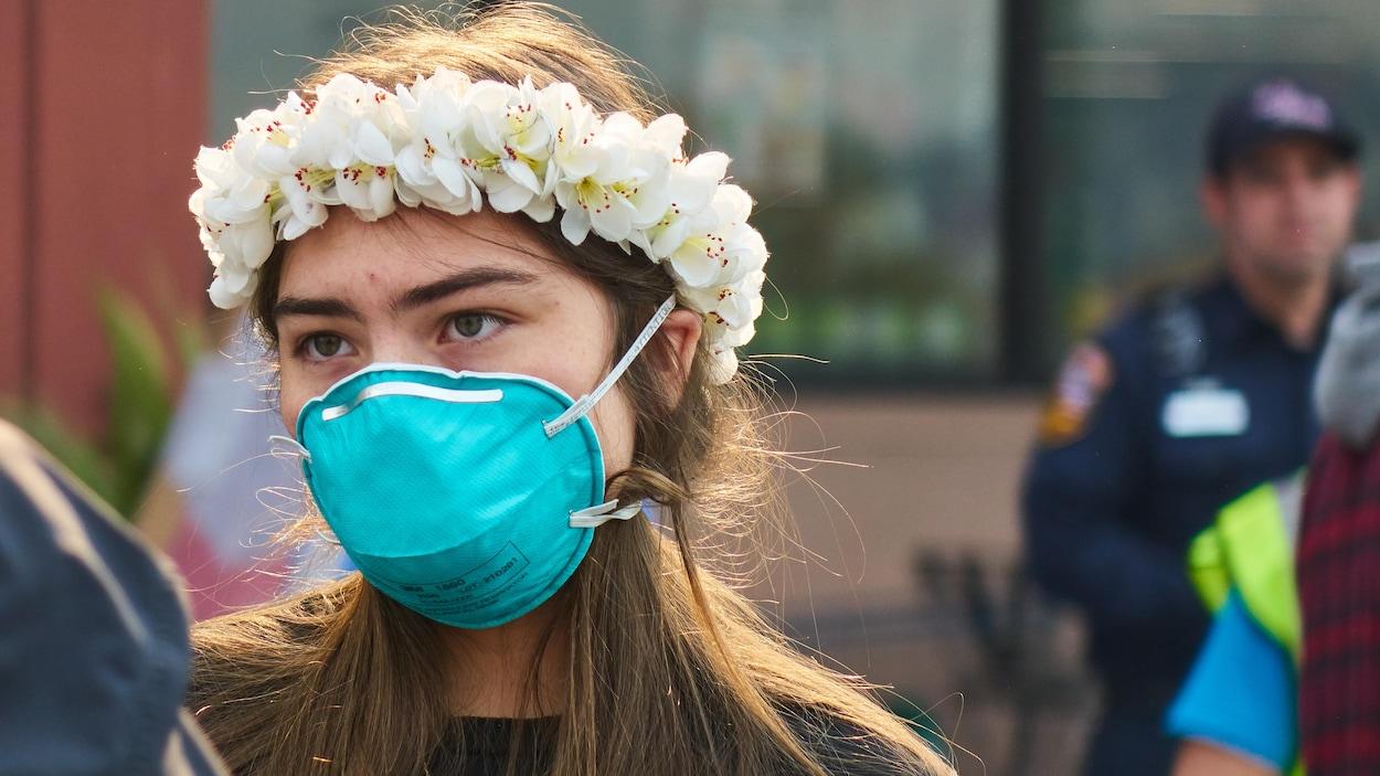 Une jeune femme portant une couronne de fleurs porte un masque respiratoire.