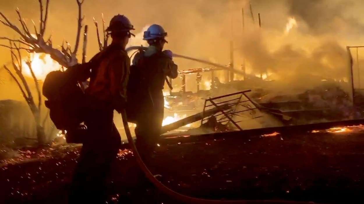 Deux pompiers tiennent une lance d'incendie à côté d'une maison détruite.