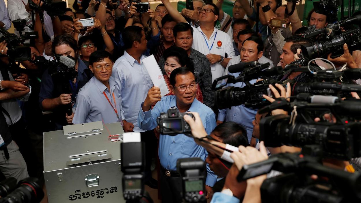 Devant des caméras, un homme s'apprête à glisser un bulletin de vote dans une urne.
