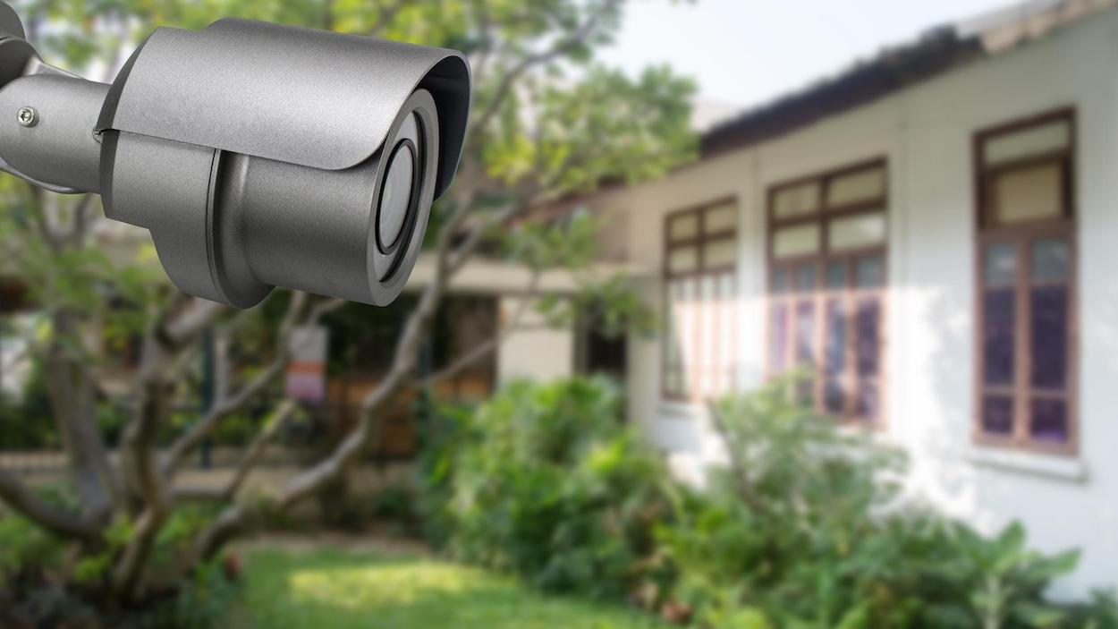 Caméra de sécurité résidentielle orientée vers une maison voisine.