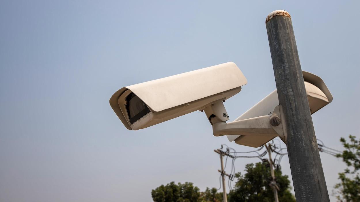 Des caméras de surveillance montées sur un poteau, à l'extérieur.