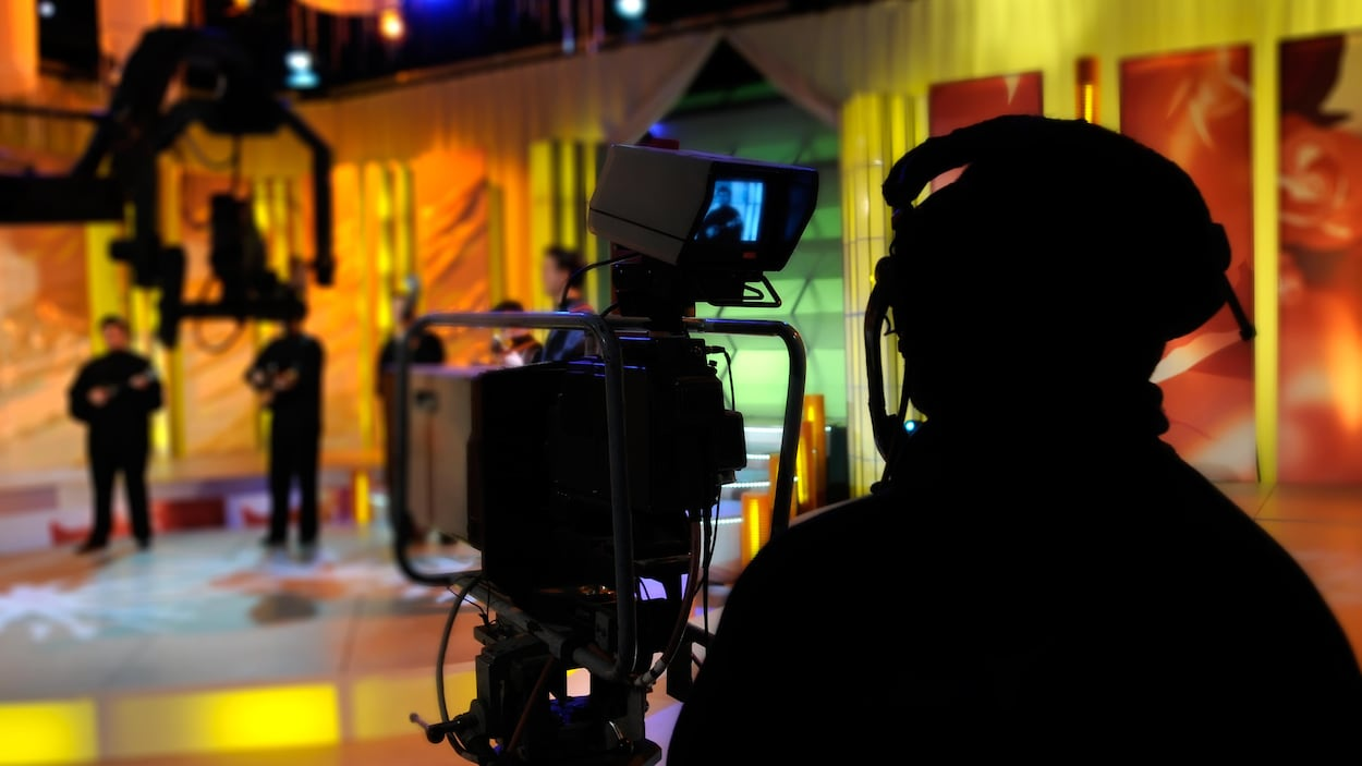 Une personne portant un casque d'écoute se tient derrière une caméra, alors qu'elle filme le plateau d'une émission de télévision.