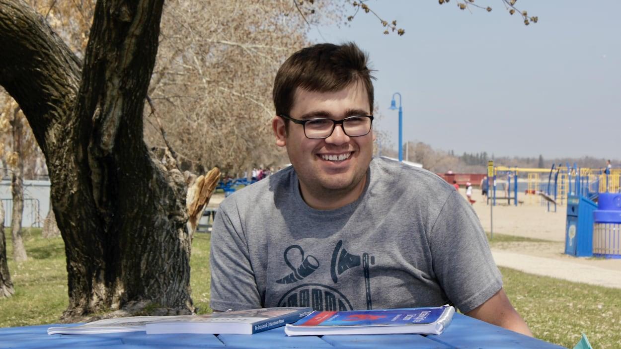 Cameron Adams, un jeune garçon autochtone, assis à une table où se trouvent des livres, devant une plage au Manitoba.