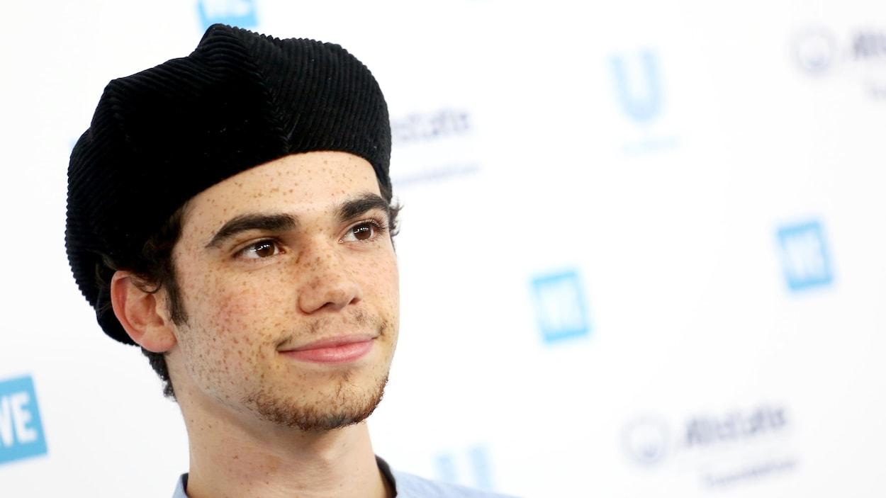 Cameron Boyce porte un béret noir et sourit légèrement en regardant droit devant lui.