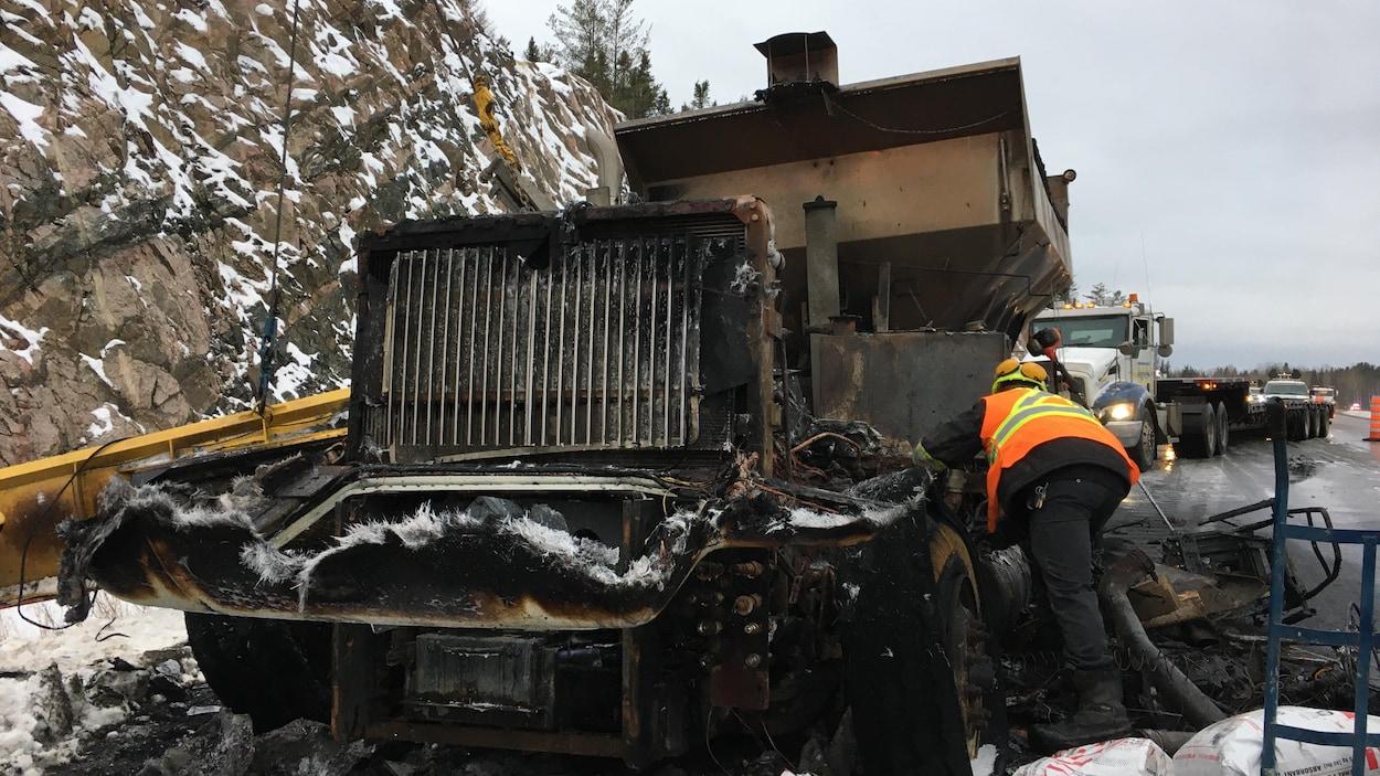 Un travailleur s'affaire autour de la carcasse du camion.