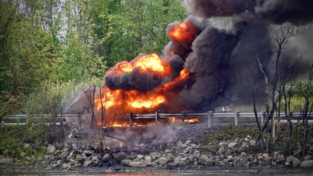Une carcasse de camion brûle sur une route, tout près d'une rivière.