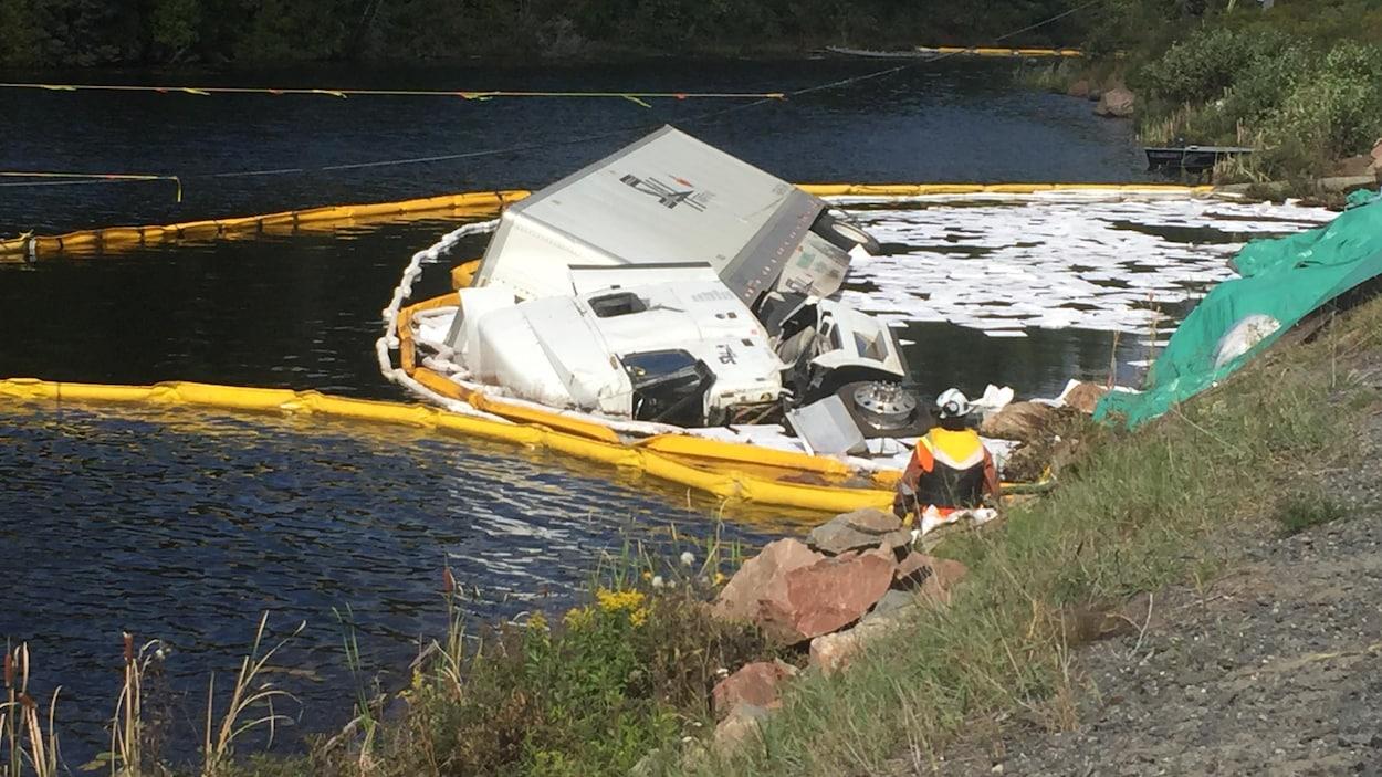 Un camion tombé dans un lac entouré de bouées antipollution.