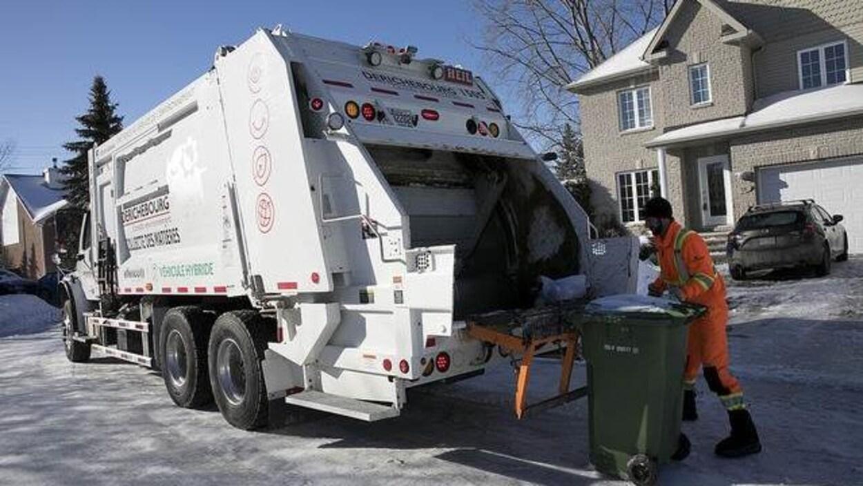 Un éboueur est en train de vider un bac à ordures à Gatineau.