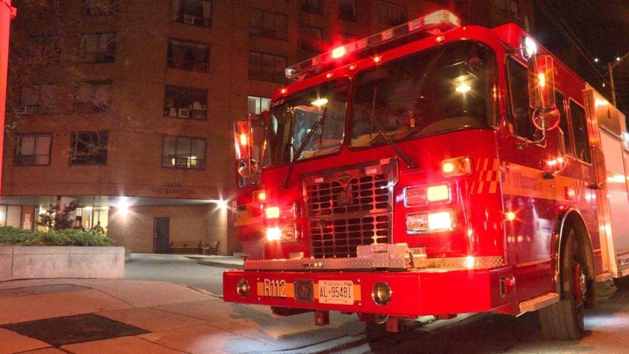 Photo d'un camion de pompier rouge aux lumières clignotantes devant un immeuble en briques brunes, le soir.