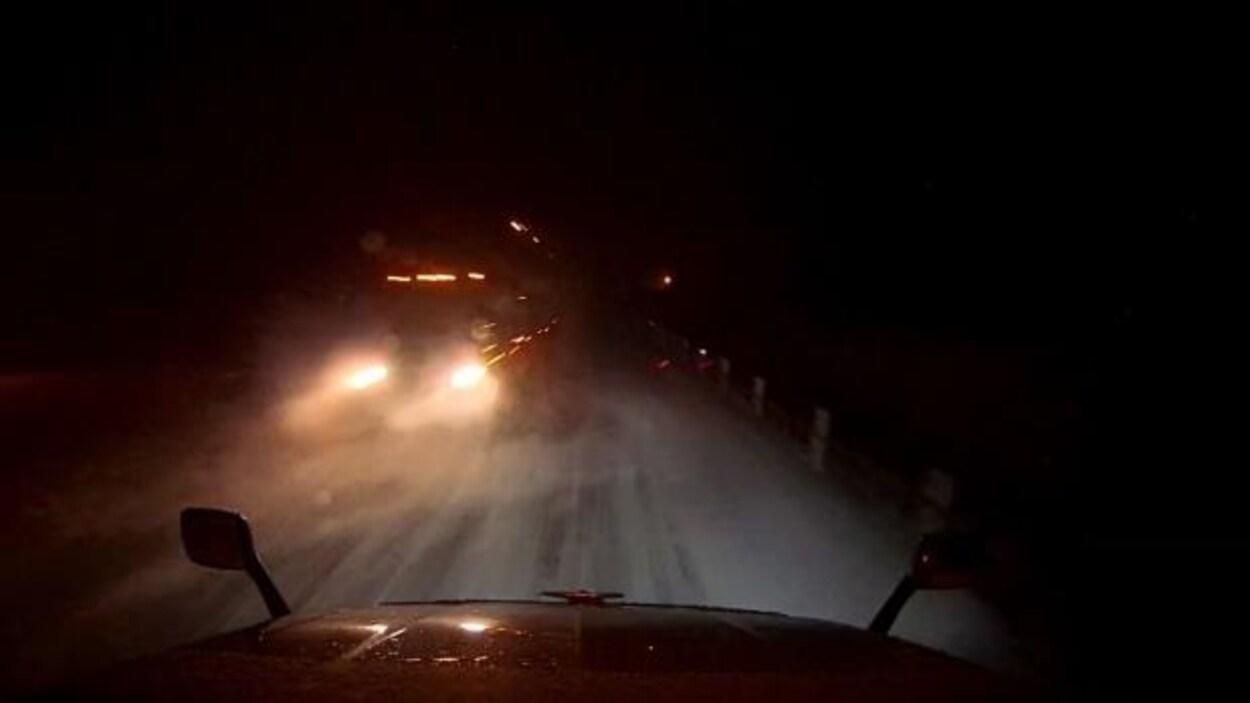 Deux camions se croisent sur une route un soir d'hiver.