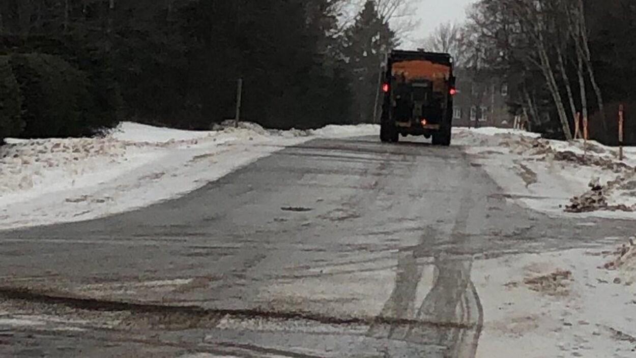 Le camion progresse lentement sur une route rurale recouverte de verglas