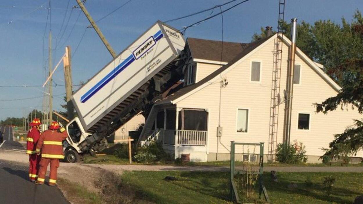 Deux pompiers regarde un camion dont l'arrière se trouve sur le toit d'une maison.