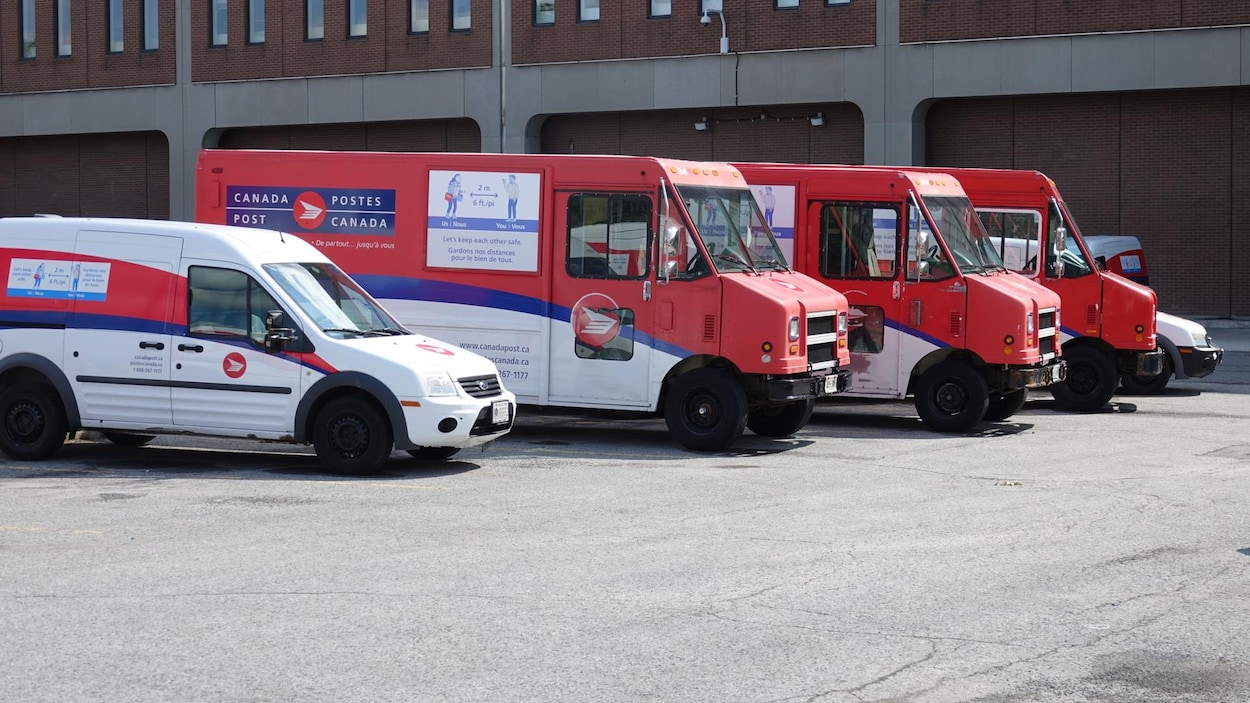 Des camions rouges de postes Canada dans un stationnement.