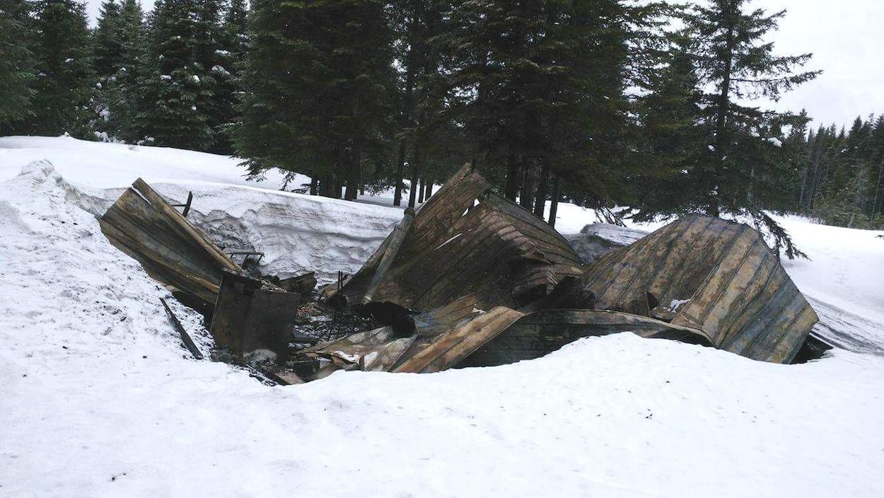 Camp de chasse carbonisé dans la neige.