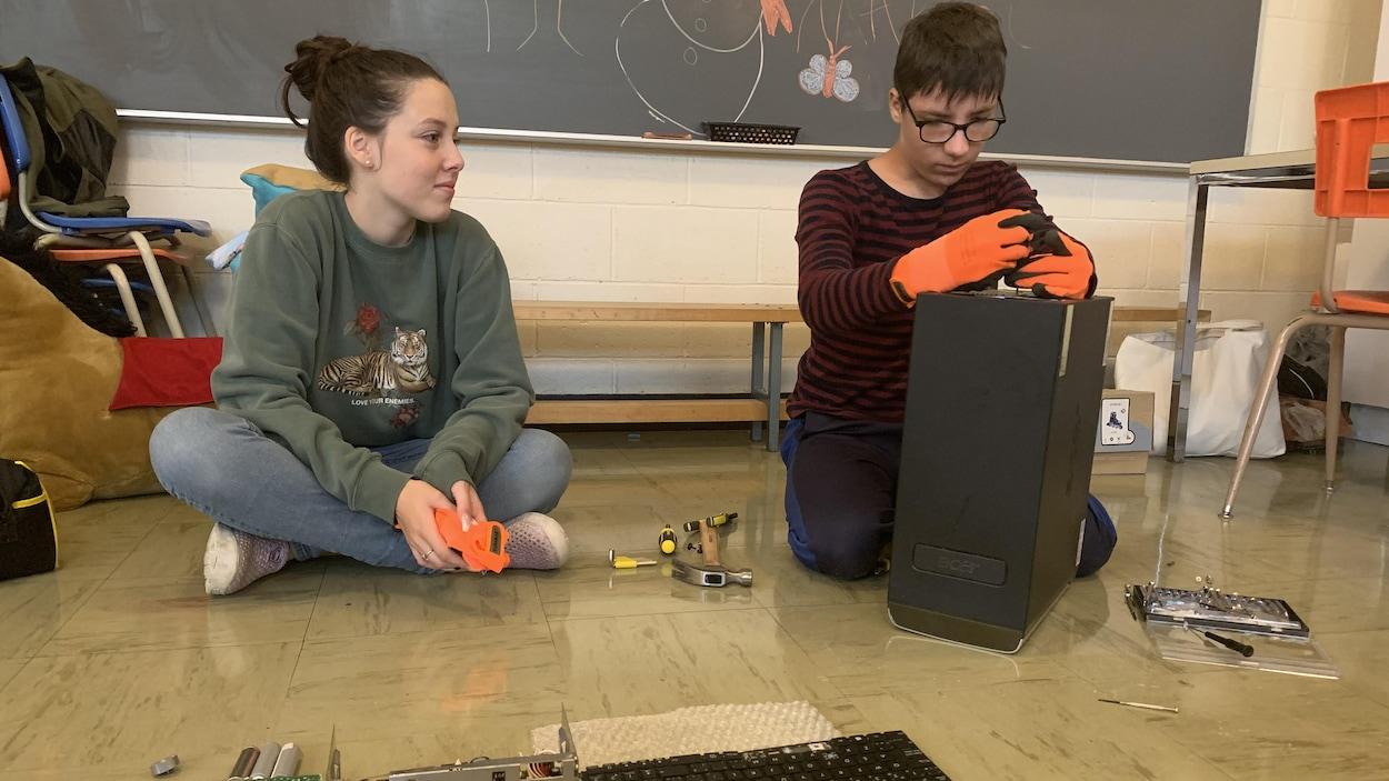 Un garçon manipule des pièces pour construire un appareil électronique et une jeune fille à côté de lui le regarde.