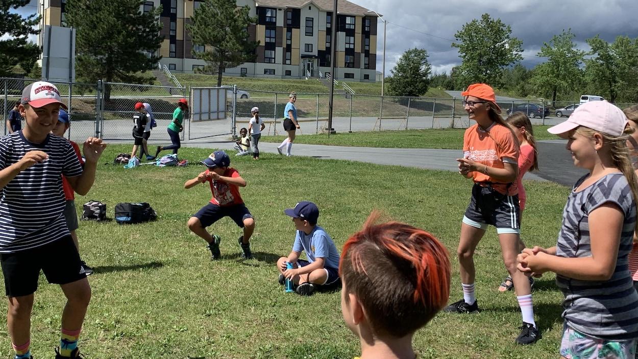 Des enfants en cercles avec une personne au milieu se regardent et attendent le signal pour jouer.