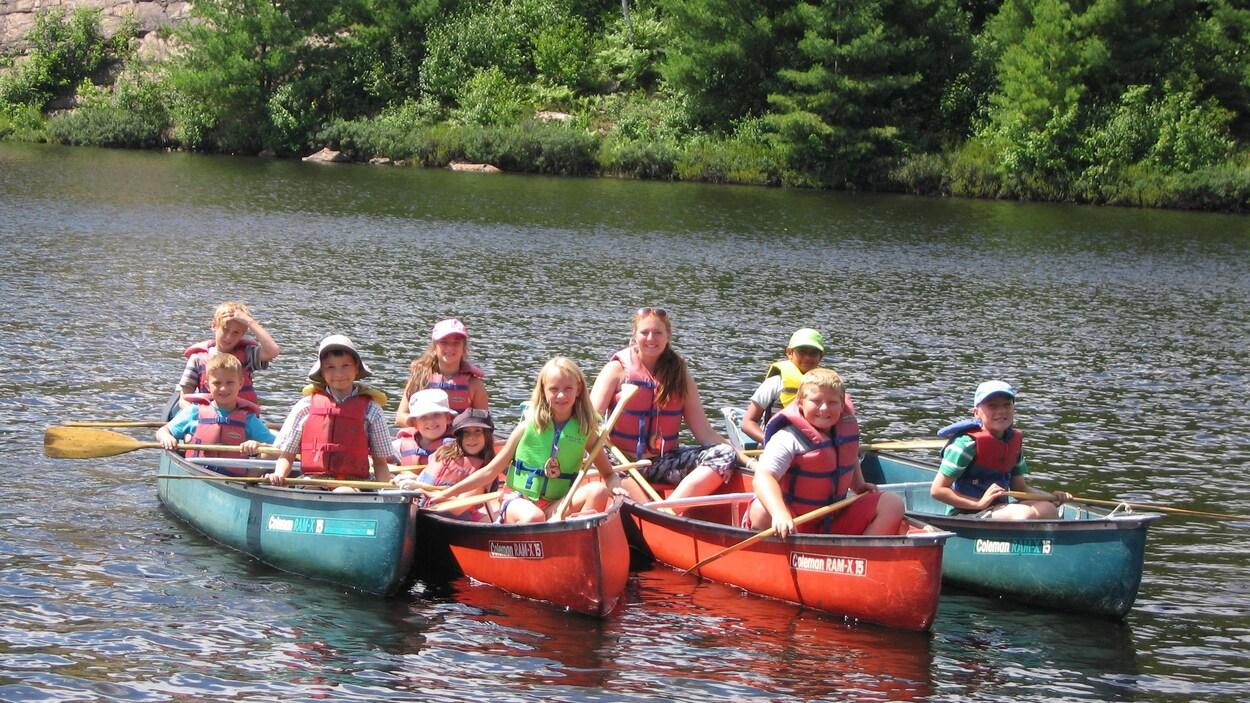Une douzaine de jeune accompagnée d'une intervenante forment se tiennent dans des canots alignés.