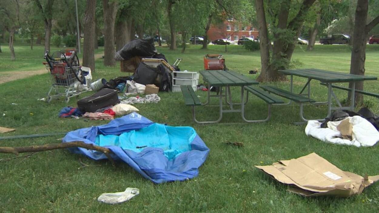 Des morceaux de carton, des bouts de tissus et des paniers sur le sol dans un parc.