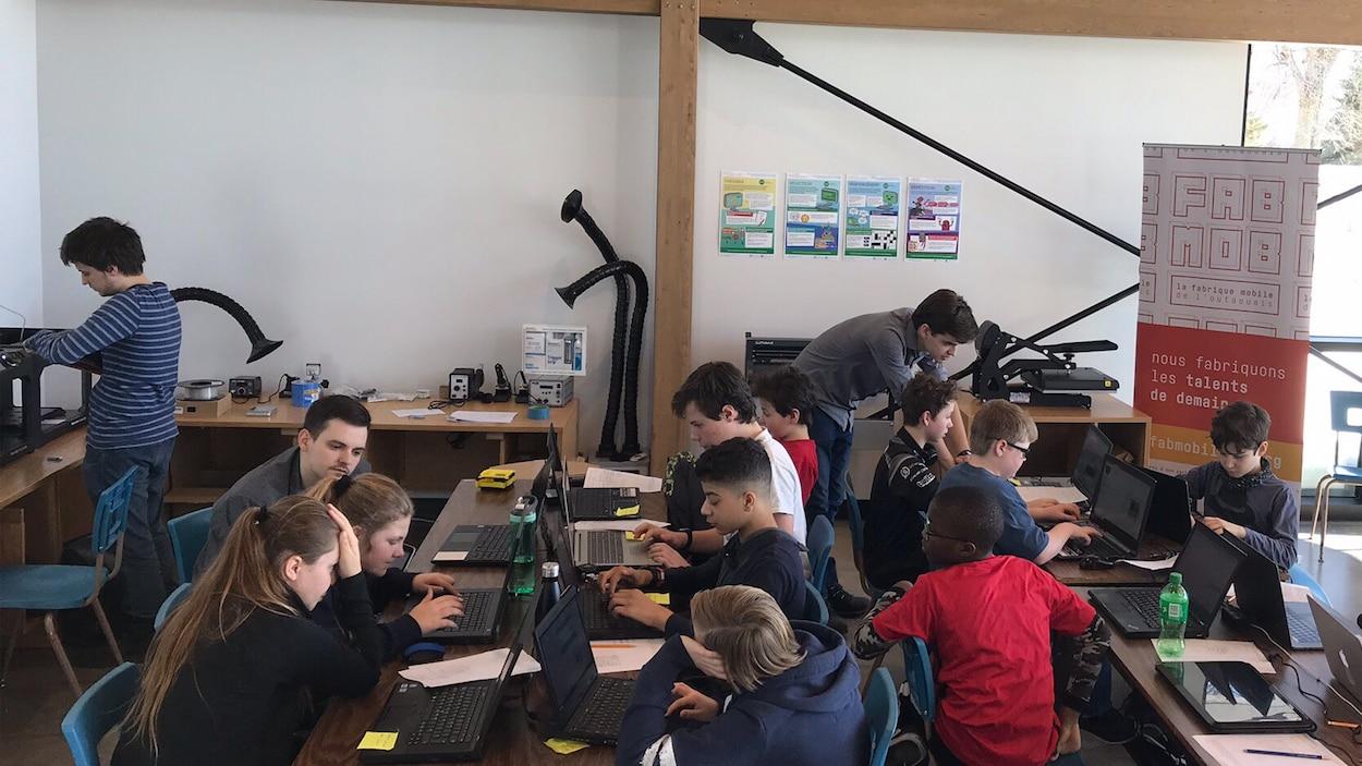 Deux groupes de jeunes travaillent sur des ordinateurs.