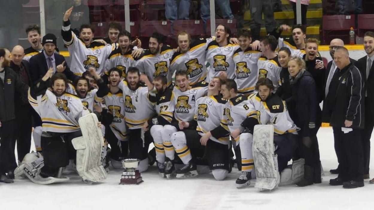 Les joueurs groupés sur la patinoires célèbrent leur victoire