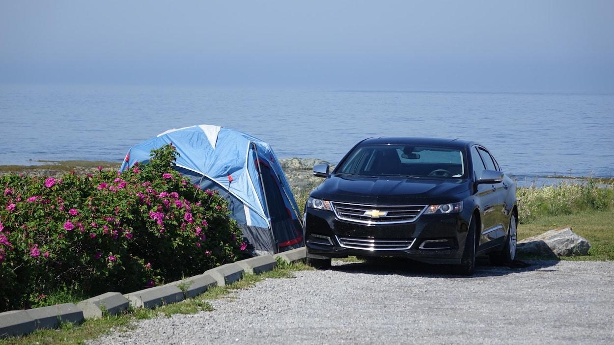 Une tente bleue montée à côté d'une voiture sur le bord de la mer.