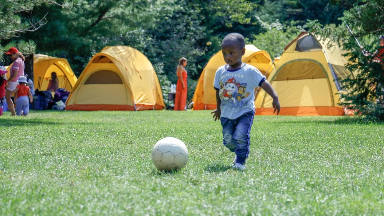 Un enfant joue avec un ballon sur un site de camping du parc national de la Mauricie.