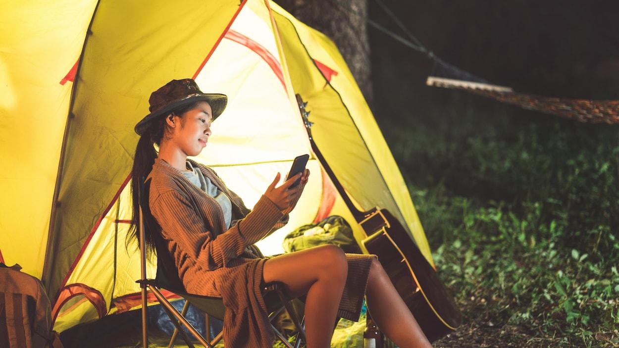Une femme asiatique consulte son téléphone cellulaire en camping