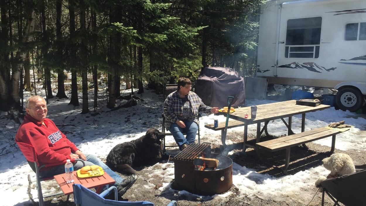 Yvon et Françoise Lambert, d'Opasatika, ainsi que leurs chiens Charlie et Midnight, sont bien heureux de se retrouver au camping au parc provincial René-Brunelle, même s'il y a encore un peu de neige autour d'eux.