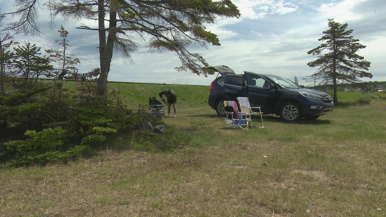 Une campeuse s'installe. On voit sa voiture, des chaises et un poêle barbecue.